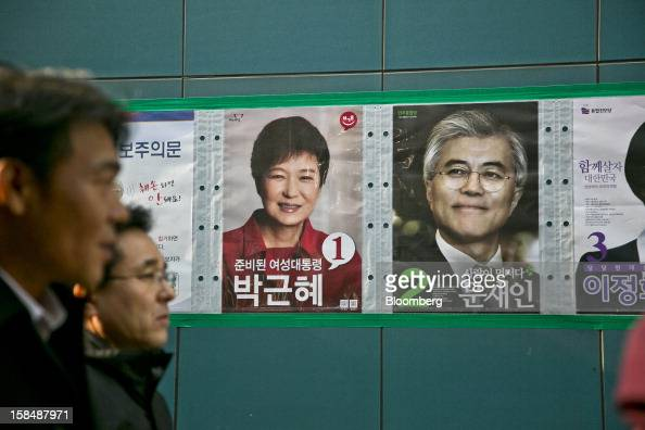 Pedestrians walk past posters of South Korean presidential candidates Park Geun Hye from the ruling New Frontier Party left and Moon Jae In from the...
