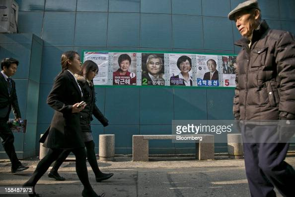 Pedestrians walk past posters of South Korean presidential candidates Park Geun Hye from the ruling New Frontier Party from left Moon Jae In from the...