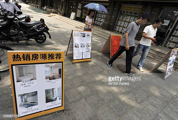 Pedestrians walk past real estate agent offices in Beijing on August 10 2010 Property prices in China rose at a slower pace in July from the previous...