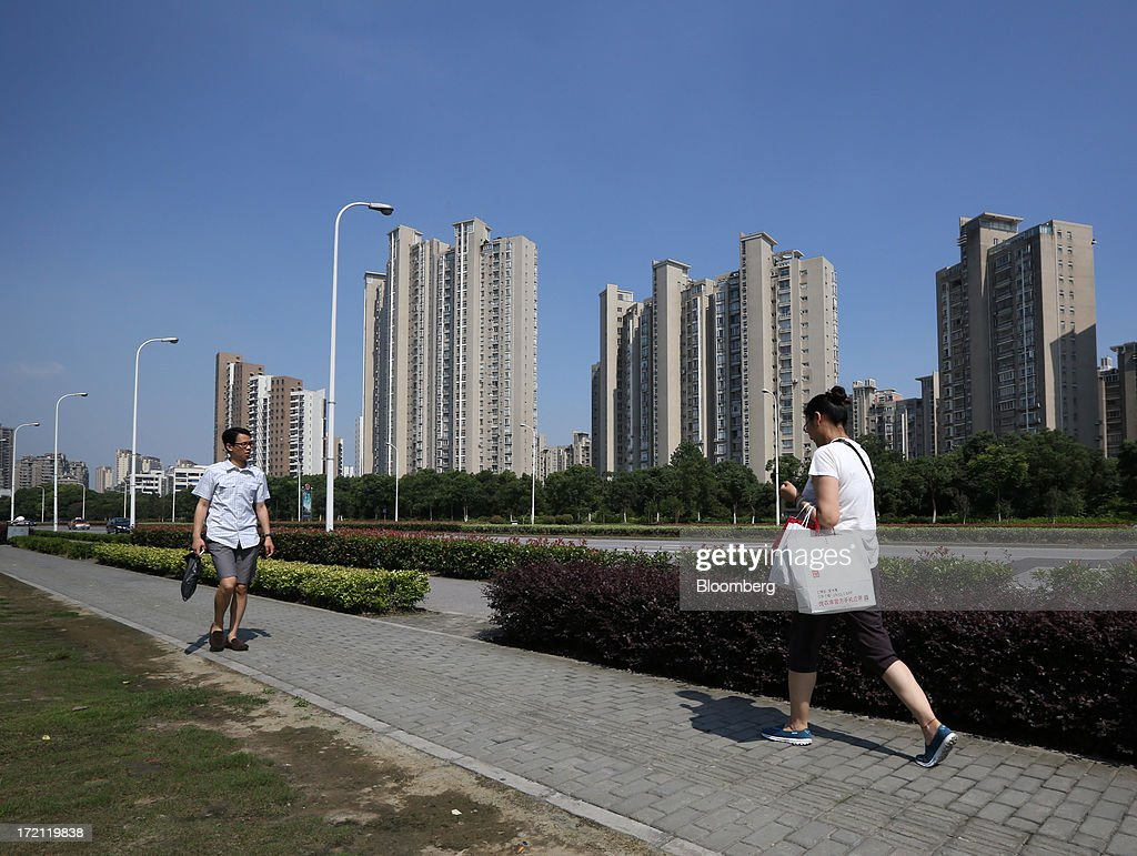 Pedestrians walk past residential buildings in Shanghai, China, on Sunday, June 30, 2013. China's President Xi Jinping said officials shouldn't be judged solely on their record in boosting gross domestic product, the latest signal that policy makers are prepared to tolerate slower economic expansion. Photographer: Tomohiro Ohsumi/Bloomberg via Getty Images