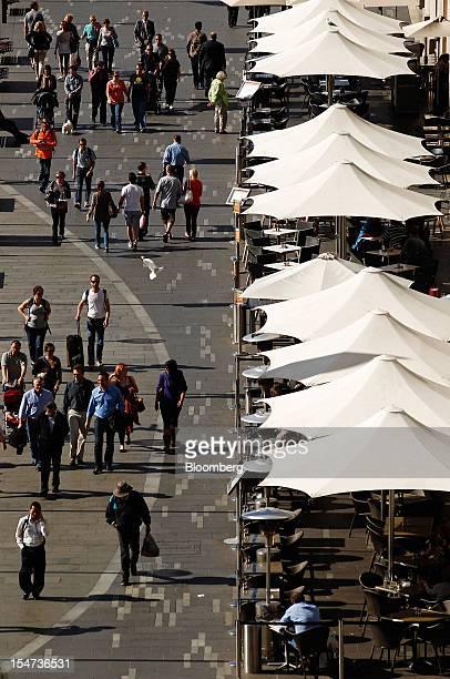 Pedestrians walk past restaurants along the promenade at East Circular Quay in Sydney Australia on Tuesday Oct 23 2012 Treasurer Wayne Swan on Monday...