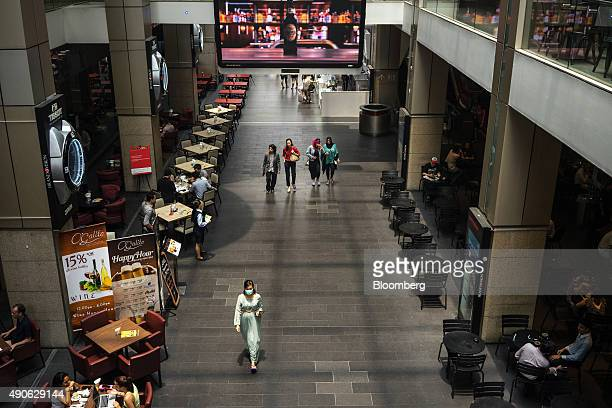 Pedestrians walk past restaurants in the Bukit Bintang area of Kuala Lumpur Malaysia on Tuesday Sept 29 2015 The ringgit's weakness slowing Chinese...