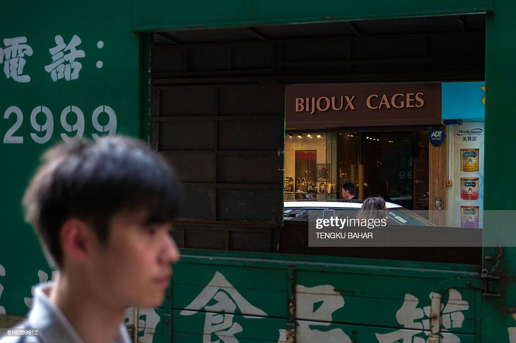 Pedestrians walk past retail shops and traffic in the Tim Sha Tsui district of Hong Kong on October 22, 2016. / AFP / TENGKU