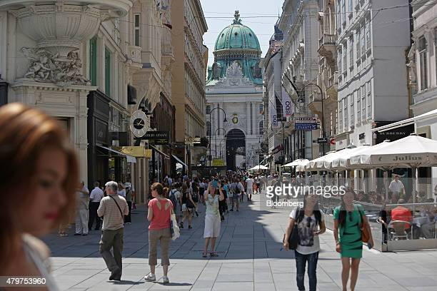 Pedestrians walk past retail stores and restaurants in front of the Hofburg palace in the Kohlmarkt area of Vienna Austria on Friday July 3 2015...