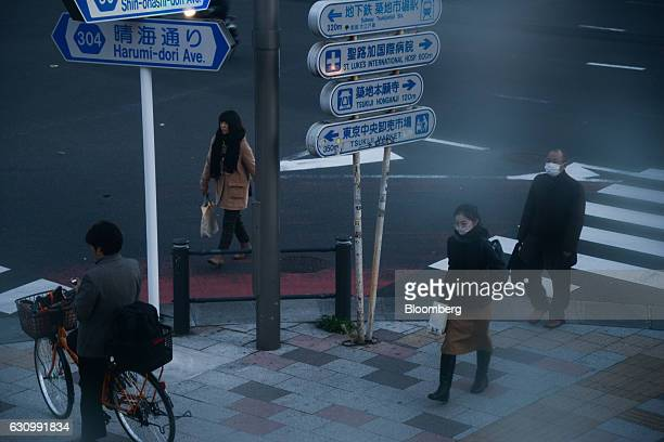 Pedestrians walk past road signs displayed outside the Tsukiji Market in Tokyo Japan on Thursday Jan 5 2017 Kiyomura KK operator of Sushi Zanmai...