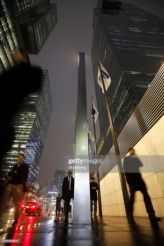 Pedestrians walk past Samsung Electronics Co.'s offices as the company's corporate flag flies in Seoul, South Korea on Wednesday, Jan. 23, 2013. Samsung, in a preliminary statement of results on Jan. 8, reported an 89 percent jump in profit in the three months ended in December, boosted by its Galaxy line of smartphones. Photographer: Woohae Cho/Bloomberg via Getty Images