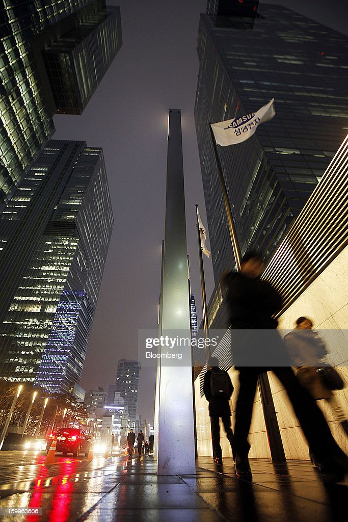 Pedestrians walk past Samsung Electronics Co.'s offices as the company's corporate flag flies in Seoul, South Korea, on Wednesday, Jan. 23, 2013. Samsung, in a preliminary statement of results on Jan. 8, reported an 89 percent jump in profit in the three months ended in December, boosted by its Galaxy line of smartphones. Photographer: Woohae Cho/Bloomberg via Getty Images