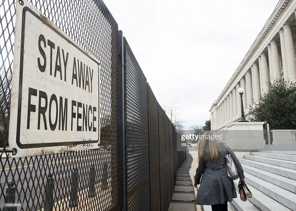 Pedestrians walk past security fencing in front of the Cannon House Office Building on Thursday, Jan. 17, 2013, as security ramps up for President Barack Obama's inauguration.