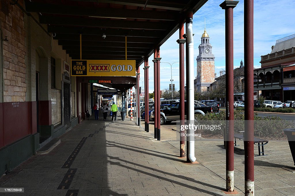 Pedestrians walk past signage for Castlemaine Perkins brewery's XXXX brand of beer across from the clock tower in the mining town of Kalgoorlie, Australia, on Thursday, Aug. 8, 2013. Western Australia, the nation's largest state by area with 2.6 million square kilometers (1 million square miles) of land, earned A$97 billion from minerals and energy sales in 2012, down from A$108 billion in 2011, according to government figures. Photographer: Carla Gottgens/Bloomberg via Getty Images