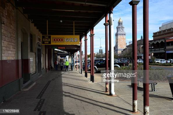 Pedestrians walk past signage for Castlemaine Perkins brewery's XXXX brand of beer across from the clock tower in the mining town of Kalgoorlie...