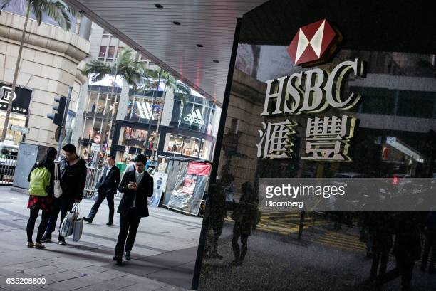 Pedestrians walk past signage for HSBC Holdings Plc displayed outside a bank branch in the Central district of Hong Kong China on Monday Feb 13 2017...
