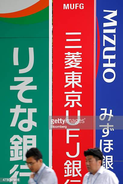 Pedestrians walk past signage for Mizuho Bank Ltd right Bank of Tokyo Mitsubishi UFJ Ltd center and Resona Bank Ltd in Tokyo Japan on Tuesday May 12...