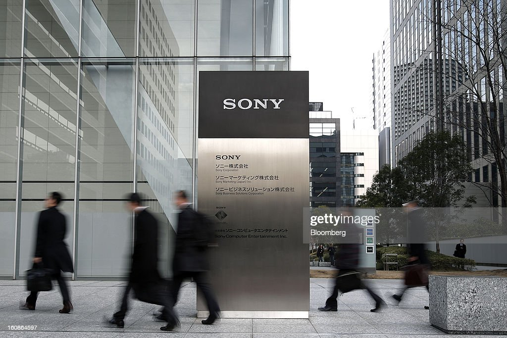 Pedestrians walk past signage for Sony Corp. outside the company's headquarters in Tokyo, Japan, on Thursday, Feb. 7, 2013. Sony, Japan's biggest consumer-electronics exporter, reported an eighth consecutive quarterly loss on waning demand for TVs and consumer preferences for devices from Apple Inc. and Samsung Electronics Co. Photographer: Kiyoshi Ota/Bloomberg via Getty Images