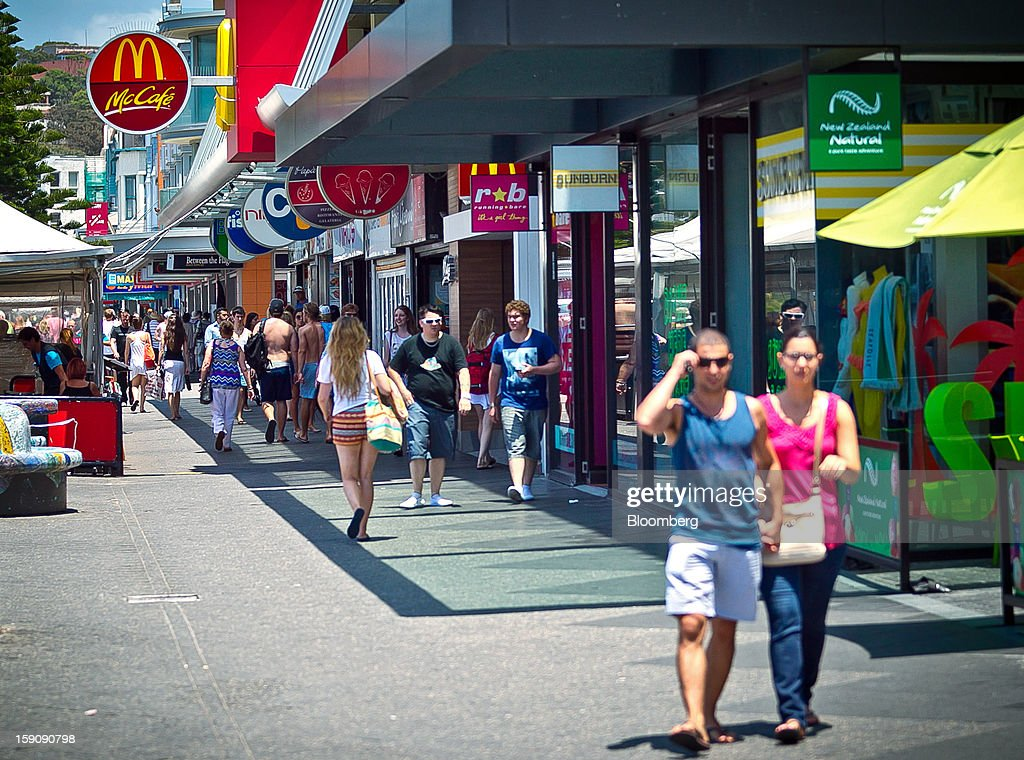 Pedestrians walk past stores and restaurants at Bondi Beach in Sydney, Australia, on Monday, Jan. 7, 2013. The Bureau of Statistics is scheduled to release retail sales data on Jan. 9. Photographer: Ian Waldie/Bloomberg via Getty Images