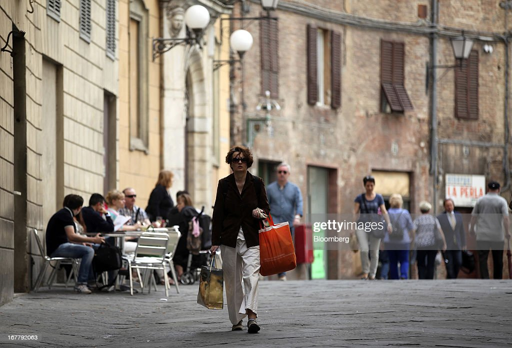 Pedestrians walk past stores and restaurants in Siena, Italy, on Monday, April 29, 2013. An Italian judge rejected a request by prosecutors to seize as much as 1.95 billion euros ($2.5 billion) of assets held by Nomura Holdings Inc. as they probed how Banca Monte dei Paschi di Siena SpA used derivatives to conceal losses. Photographer: Alessia Pierdomenico/Bloomberg via Getty Images