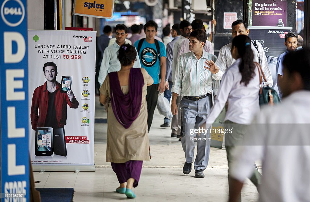 Pedestrians walk past stores displaying signage for Dell Inc. and an advertisement for Lenovo Group Ltd.'s A1000 tablet in Nehru Place IT Market, a hub for the sale of electronic goods and computer accessories, in downtown New Delhi, India, on Wednesday, Aug. 7, 2013. India's consumer price index (CPI) figures for July are scheduled to be released on August 12. Photographer: Graham Crouch/Bloomberg via Getty Images