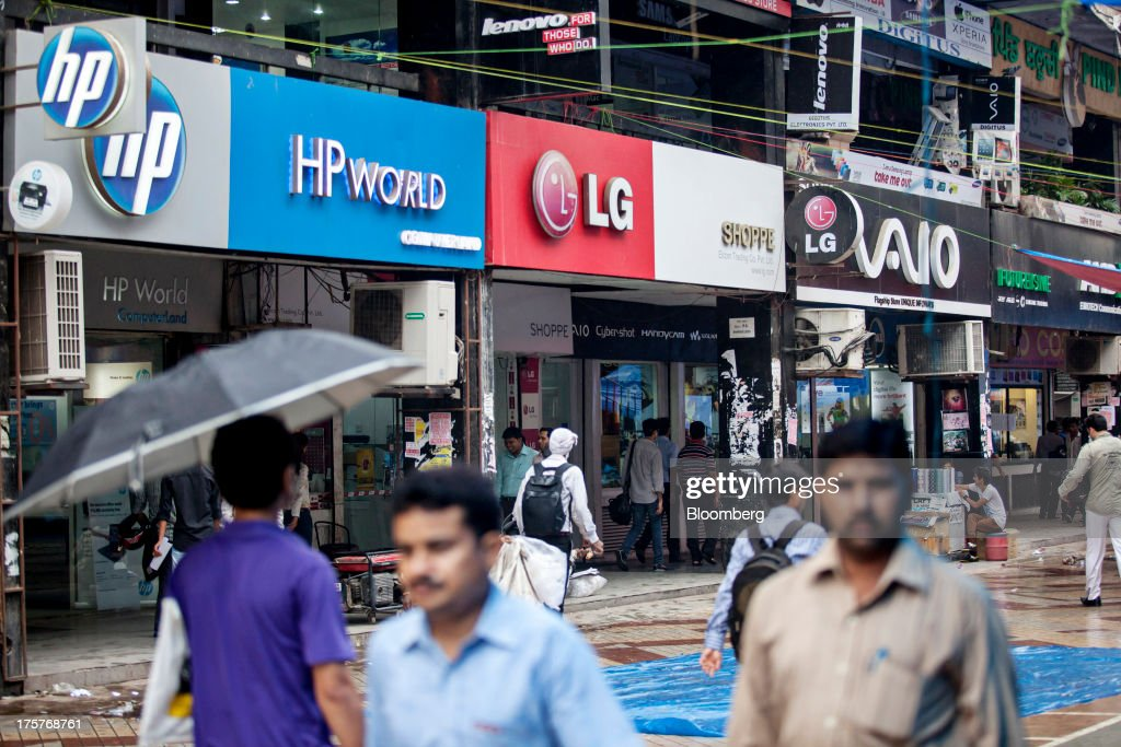 Pedestrians walk past stores displaying signage for Hewlett-Packard Co., LG ELectronics Inc. and Sony Corp.'s Vaio computer products brand in Nehru Place IT Market, a hub for the sale of electronic goods and computer accessories, in downtown New Delhi, India, on Wednesday, Aug. 7, 2013. India's consumer price index (CPI) figures for July are scheduled to be released on August 12. Photographer: Graham Crouch/Bloomberg via Getty Images