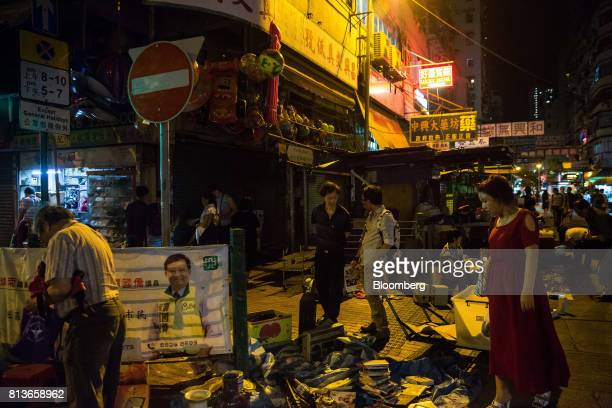 Pedestrians walk past street stalls at night in the Sham Shui Po district of Hong Kong China on Thursday May 18 2017 Sham Shui Po is a district of...