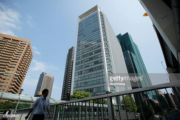 Pedestrians walk past the Ark Hills South Tower building which houses the Takata Corp headquarters center in Tokyo Japan on Thursday June 25 2015...