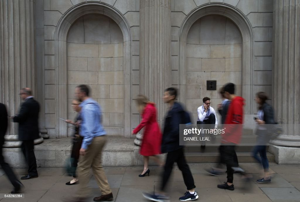 Pedestrians walk past the Bank of England in central London on June 27, 2016. Britain should only trigger Article 50 to leave the EU when it has a 'clear view' of how its future in the bloc looks, finance minister George Osborne said Monday following last week's shock referendum. London stocks extended their losses in early afternoon Monday, led by banking, airline and property shares, following Britain's vote to leave the EU. / AFP / Daniel Leal-Olivas