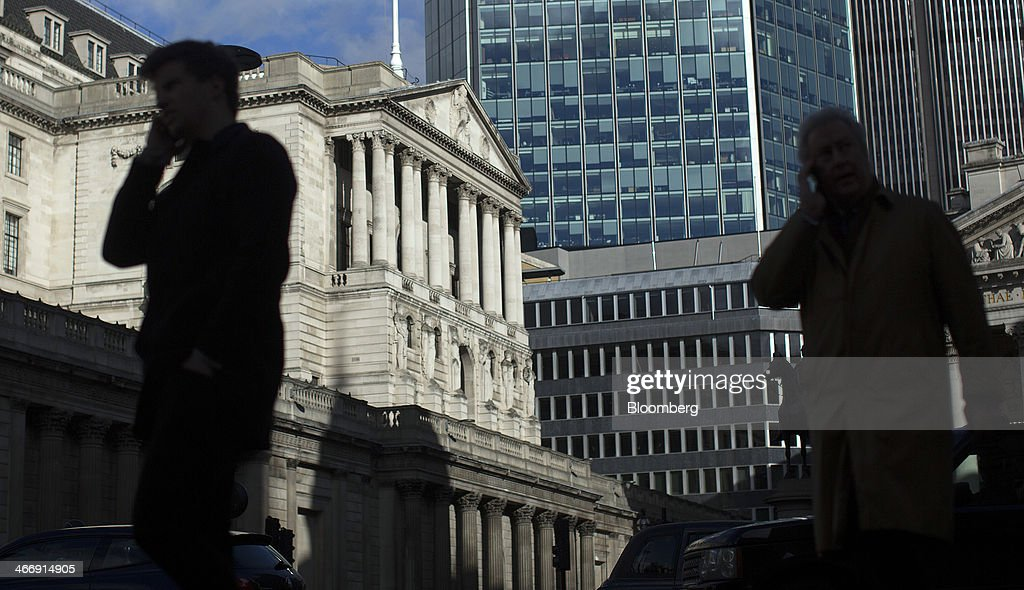 Pedestrians walk past the Bank of England in London, U.K., on Tuesday, Feb. 4, 2014. Between 2007 and 2011, policy makers in London lagged behind their American counterparts in cutting rates and adopting emergency policy measures in response to the financial crisis. Photographer: Simon Dawson/Bloomberg via Getty Images