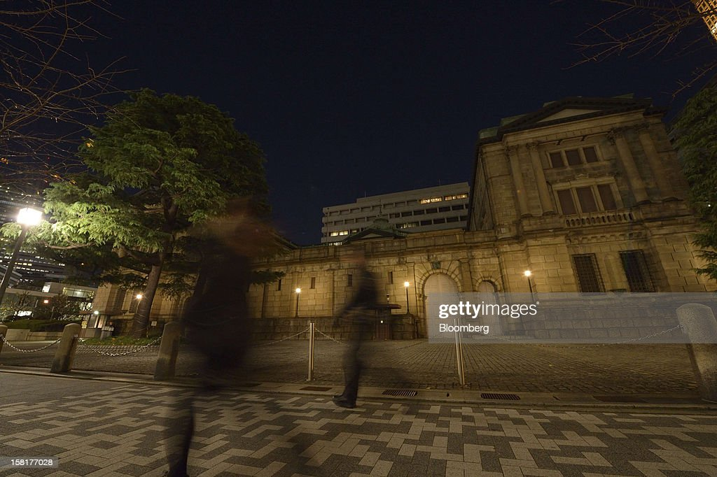 Pedestrians walk past the Bank of Japan headquarters at night in Tokyo, Japan, on Monday, Dec. 10, 2012. Japan's bond market is signaling concern that a government run by Shinzo Abe will ramp up spending to revive growth, adding to a debt burden already twice the size of the nation's economy. Photographer: Akio Kon/Bloomberg via Getty Images