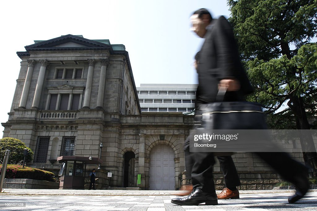 Pedestrians walk past the Bank of Japan headquarters in Tokyo, Japan, on Friday, May 21, 2010. The Bank of Japan said it will provide one-year loans to banks to encourage lending and defeat deflation, and raised its assessment of the export-led recovery. Photographer: Kiyoshi Ota/Bloomberg via Getty Images