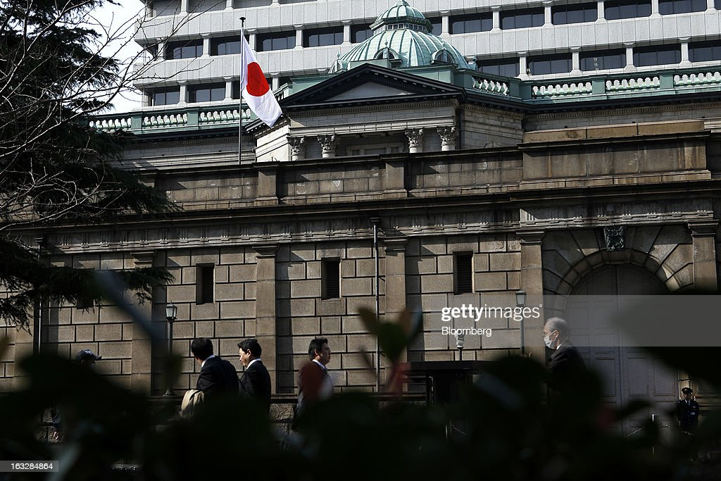 Pedestrians walk past the Bank of Japan headquarters in Tokyo, Japan, on Thursday, March 7, 2013. The Bank of Japan rejected a call for an immediate start to open-ended asset purchases in Governor Masaaki Shirakawa's final meeting before a new leadership takes over at the central bank. Photographer: Kiyoshi Ota/Bloomberg via Getty Images