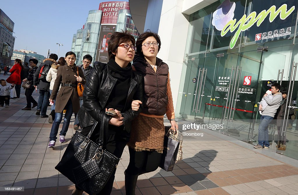 Pedestrians walk past the Beijing apm shopping mall, operated by Sun Hung Kai Properties Ltd., in the Wangfujing shopping district of Beijing, China, on Sunday, March 10, 2013. China's industrial output had the weakest start to a year since 2009 and lending and retail sales growth slowed, toughening challenges for a new leadership that wants to narrow the gap between rich and poor. Photographer: Tomohiro Ohsumi/Bloomberg via Getty Images