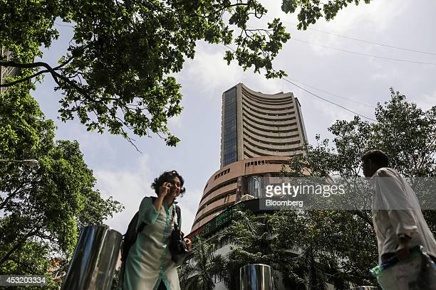 Pedestrians walk past the Bombay Stock Exchange in Mumbai India on Tuesday Aug 5 2014 Indias benchmark stockindex fell as lenders declined after the...