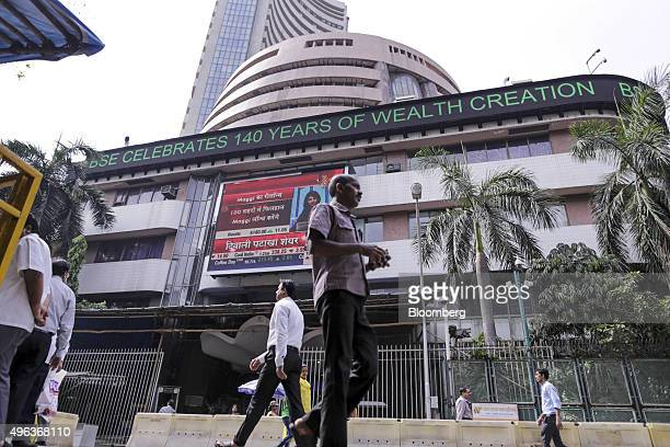 Pedestrians walk past the Bombay Stock Exchange in Mumbai India on Monday Nov 9 2015 India's rupee fell the most since August while stocks and bonds...