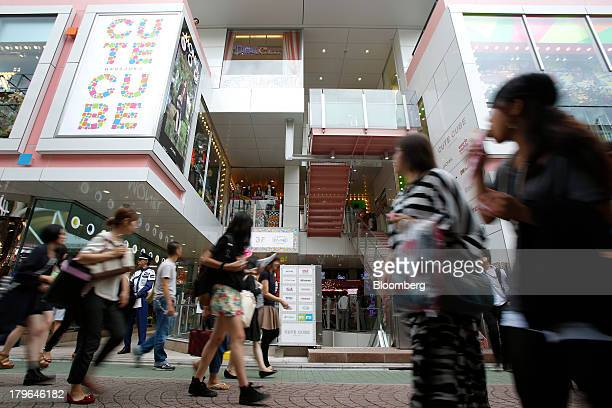 Pedestrians walk past the Cute Cube Harajuku commercial complex in the shopping district of Harajuku in Tokyo Japan on Friday Sept 6 2013 Japan's...