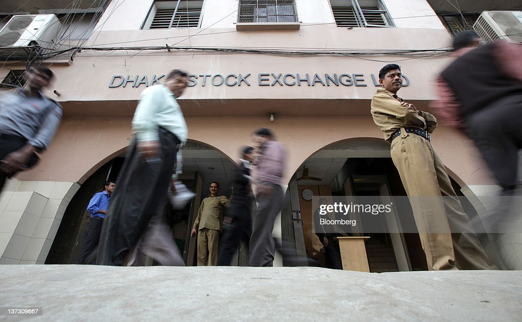 Pedestrians walk past the Dhaka Stock Exchange in Dhaka, Bangladesh, on Sunday, Jan. 8, 2012. Bangladesh's central bank this month raised interest rates for the second time in four months to curb inflation that has exceeded 9 percent since the start of 2011. Photographer: Tomohiro Ohsumi/Bloomberg via Getty Images