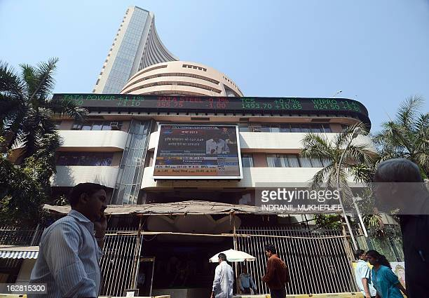 Pedestrians walk past the digital broadcast on the facade of the Bombay Stock Exchange telecasting Indian Finance Minister P Chidambaram delivering...