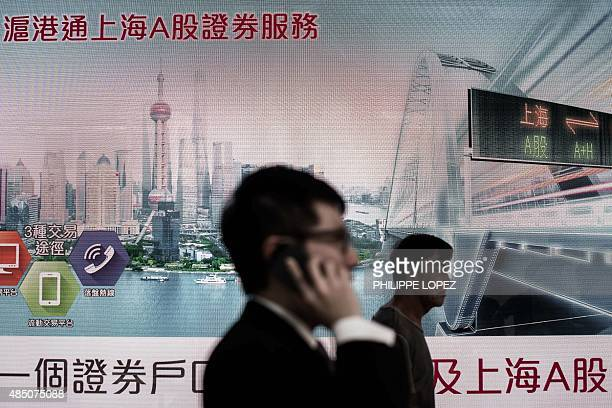 Pedestrians walk past the electronic board of a bank displaying an image of the Shanghai skyline in Hong Kong on August 24 2015 Hong Kong shares...