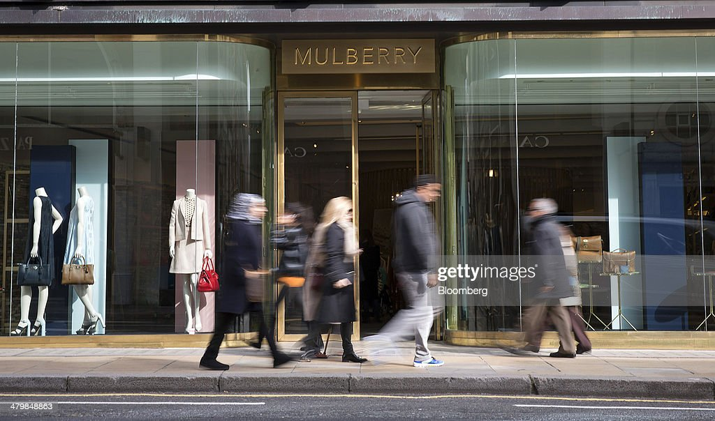 Pedestrians walk past the entrance to a Mulberry Group Plc luxury store on New Bond Street in London, U.K., on Thursday, March 20, 2014. Mulberry Group said Bruno Guillon will step down as chief executive officer after two years during which the British luxury handbag maker lost two-thirds of its market value. Photographer: Simon Dawson/Bloomberg via Getty Images