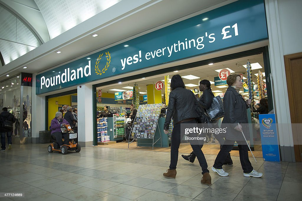 Pedestrians walk past the entrance to a Poundland discount store, operated by Poundland Group Plc in London, U.K., on Friday, March 7, 2014. Poundland Group Plc has demand for all the shares it is selling in an initial public offering that will value the U.K. discount retailer at as much as 750 million pounds ($1.3 billion), according to terms of the deal. Photographer: Simon Dawson/Bloomberg via Getty Images