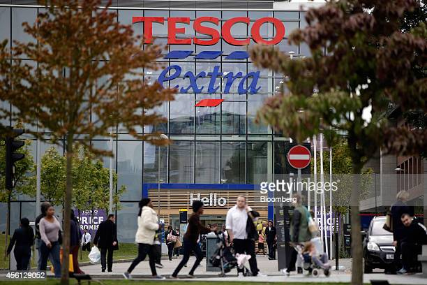 Pedestrians walk past the entrance to a Tesco Extra supermarket store operated by Tesco Plc in the Woolwich district of London UK on Thursday Sept 25...