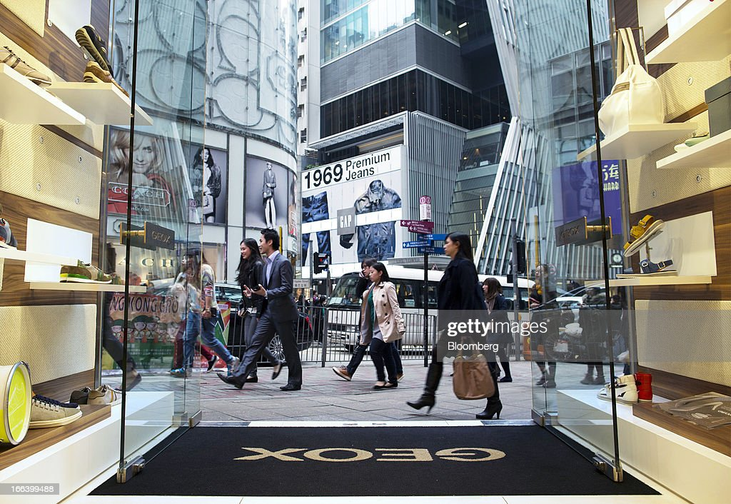 Pedestrians walk past the entrance to the Geox SpA flagship store in the Central district of Hong Kong, China, on Friday, April 12, 2013. Hong Kong's economy expanded 1.4 percent in 2012 and Financial Secretary John Tsang is projecting growth of 1.5 percent to 3.5 percent this year. Photographer: Jerome Favre/Bloomberg via Getty Images