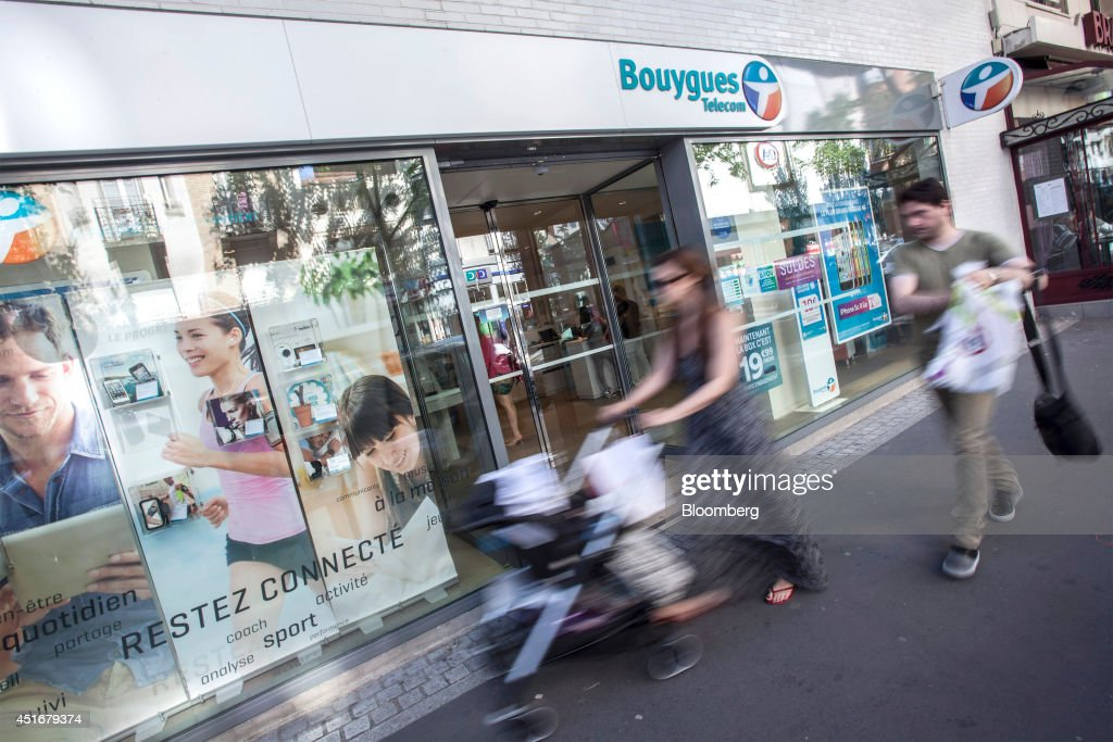 Pedestrians walk past the exterior of a Bouygues Telecom store, operated by Bouygues SA in Paris, France, on Thursday, July 3, 2014. Bouygues Telecom, France's third-largest mobile operator, was looking for a buyer as profitability and cash generation declined. Photographer: Balint Porneczi/Bloomberg via Getty Images