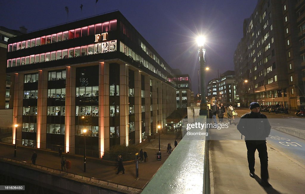 Pedestrians walk past the Financial Times newspaper's headquarters which are bathed in pink light to mimic the color of the publication's paper, as part of their 125th anniversary celebrations, in London, U.K. on Wednesday, Feb. 13, 2013. Pearson Plc, owner of the Financial Times newspaper, cut its forecast for 2012 and predicted a difficult 2013, as tougher market conditions hit earnings at its professional education and FT Group units. Photographer: Chris Ratcliffe/Bloomberg via Getty Images