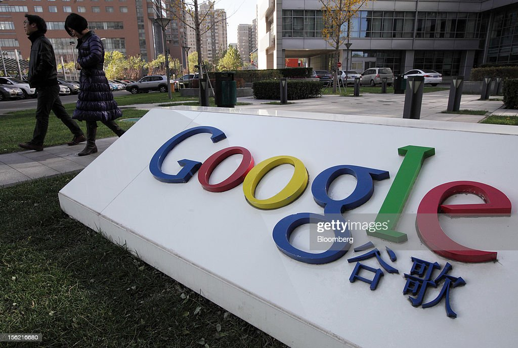 Pedestrians walk past the Google Inc. logo displayed outside the building housing the company's China headquarters in Beijing, China, on Monday, Nov. 12, 2012. Google Inc. reported higher traffic patterns on its sites in China after the company earlier said there was an unusual decline in the country, and an Internet monitor said company services were blocked there. Photographer: Tomohiro Ohsumi/Bloomberg via Getty Images