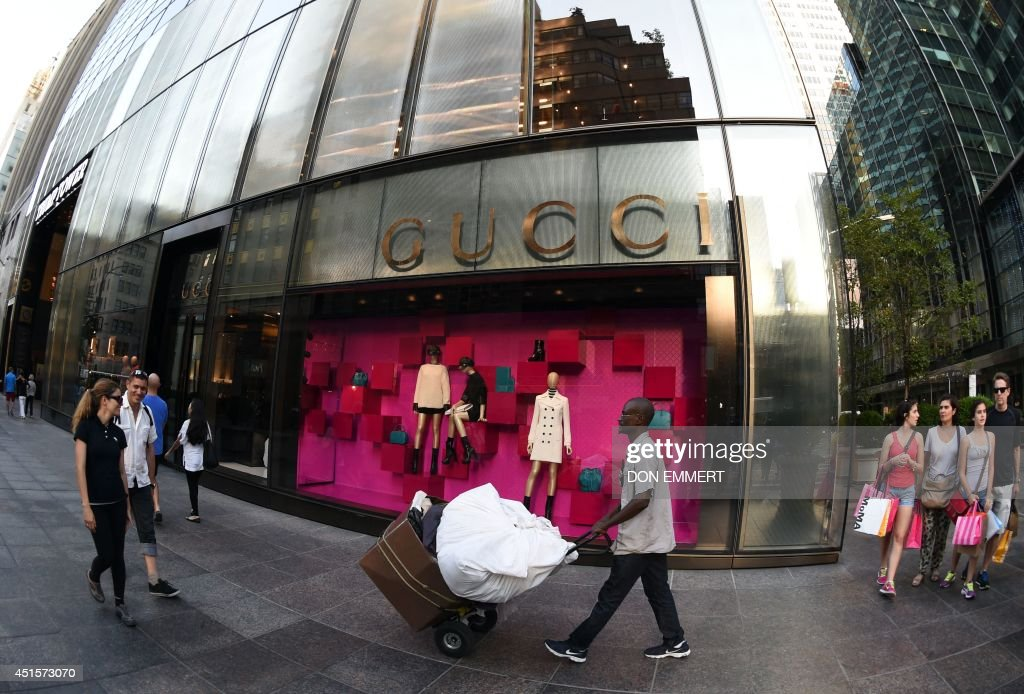 Pedestrians walk past the Gucci store on Fifth Avenue in New York on June 30, 2014. A The glass structure, at the base of the Trump Tower, is Guccis newest store. AFP PHOTO/Don Emmert