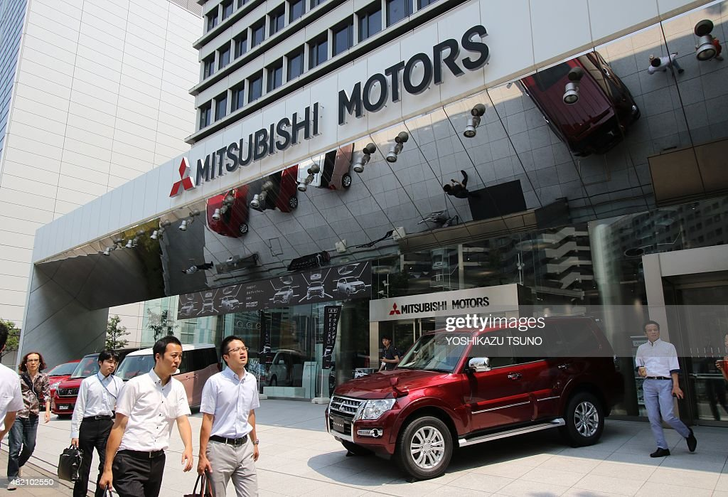 Pedestrians walk past the headquarters of Japanese automaker Mitsubishi Motors in Tokyo on July 27 2015 Mitsubishi will end vehicle production in the...
