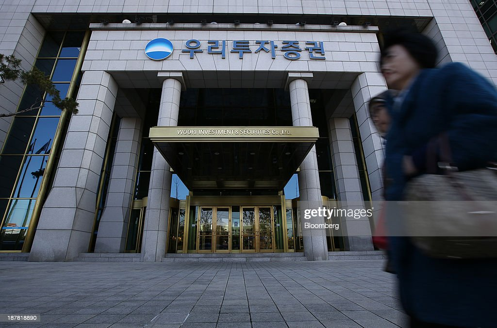 Pedestrians walk past the headquarters of Woori Investment & Securities Co., a unit of Woori Finance Holdings Co., in Seoul, South Korea, on Tuesday, Nov. 12, 2013. Woori Finance Holdings is scheduled to report third-quarter results on Nov. 14. Photographer: SeongJoon Cho/Bloomberg via Getty Images