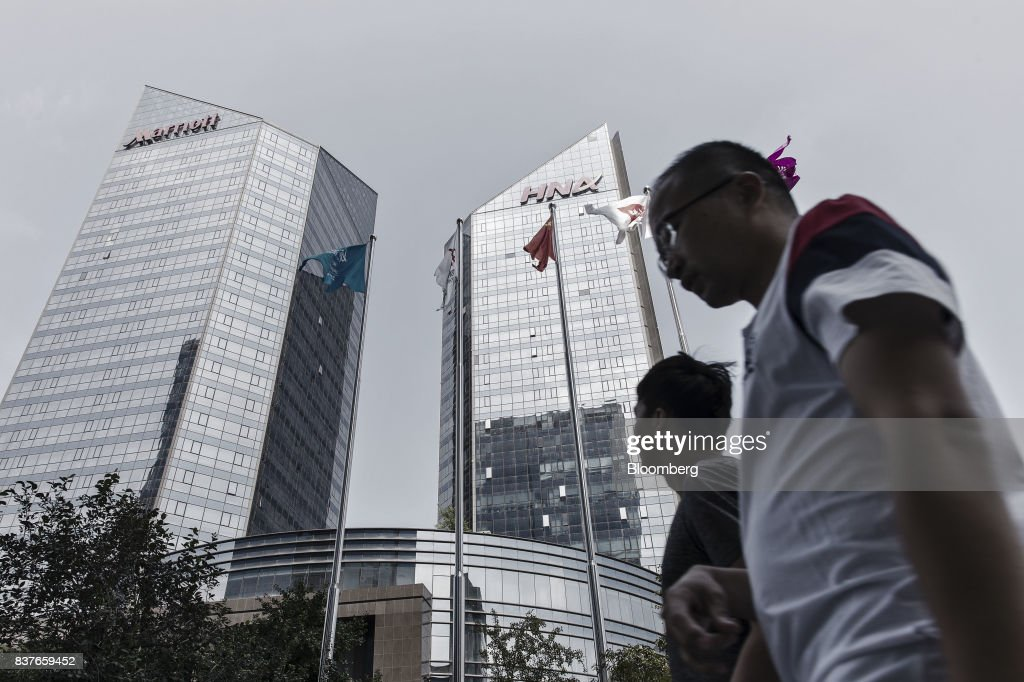 Pedestrians walk past the HNA Group Co. building in Beijing, China, on Wednesday, Aug. 9, 2017. Big Chinese dealmakers including HNA have been under increasing scrutiny this year as the Communist Party steps up its clampdown of capital outflows to protect the yuan from weakening further. Photographer: Qilai Shen/Bloomberg via Getty Images