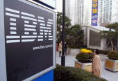 Pedestrians walk past the IBM logo in front of the head quarters January 5 2004 in Seoul South Korea South Korean prosecutors have indicted 48 people...