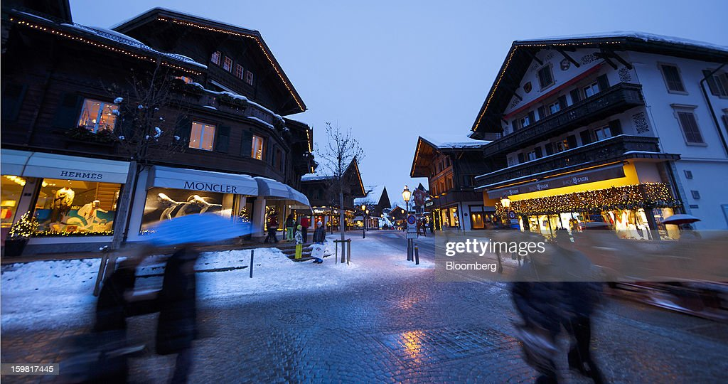 Pedestrians walk past the illuminated windows of stores advertising Hermes and Moncle SpA brands on the promenade in Gstaad, Switzerland, on Saturday, Jan. 19, 2013. Options traders are pushing the cost of bearish wagers on Swiss shares to the lowest level in almost seven years amid optimism a decline in the franc versus the euro will benefit the nation's exporters. Photographer: Valentin Flauraud/Bloomberg via Getty Images