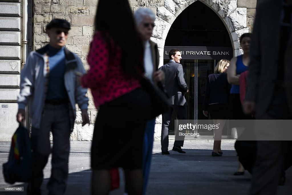 Pedestrians walk past the Leumi Private bank, a unit of Bank Leumi Le-Israel, in Geneva, Switzerland, on Wednesday, June 5, 2013. Members of the Swiss parliament's upper house's economic committee have been debating a law which, if passed, could authorize Swiss banks to cooperate with U.S. authorities. Photographer: Valentin Flauraud/Bloomberg via Getty Images