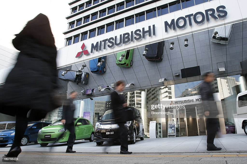 Pedestrians walk past the Mitsubishi Motors Corp. headquarters in Tokyo, Japan, on Tuesday, Feb. 5, 2013. Shares in Mitsubishi Motors dropped after the company reduced its operating profit forecast. Photographer: Kiyoshi Ota/Bloomberg via Getty Images